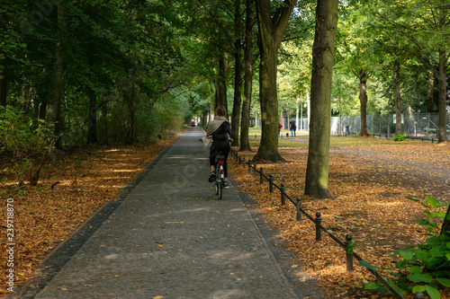 Tiergarten park, Berlin. Healthy lifestyle concept. Woman is cycling on a path. Forest at autumn background.