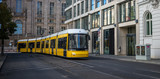Public transportation concept. Yellow electric tram travels at Berlin's town, Germany. Buildings background, banner.