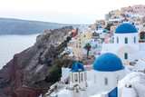 Whitewashed houses and blue dome church by the Aegean sea, Santoriniin Oia, Santorini, Greece. Famous blue domes in Oia village, Santorini, Greece - Immagine - 239756895