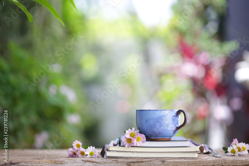 Old blue cup and notebook with flower on wooden table - 239781226