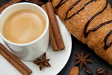Breakfast set. Coffee with croissant decorated with cinnamon quills and star anise