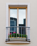 french style balcony windows with geranium flower pots, house facade detail