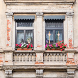 windows with geranium flower pots, old house facade detail