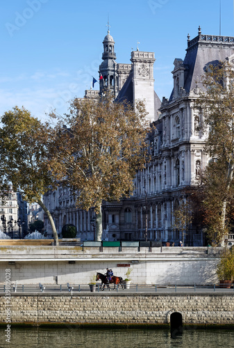 obraz PCV mounted police patrol along the Seine river quay and Paris city hall