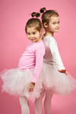 two cute little girls in white tulle skirts on a pink background