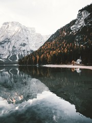 Calm morning at the Braies lake in autumn.Beautiful mountain reflections on water.
