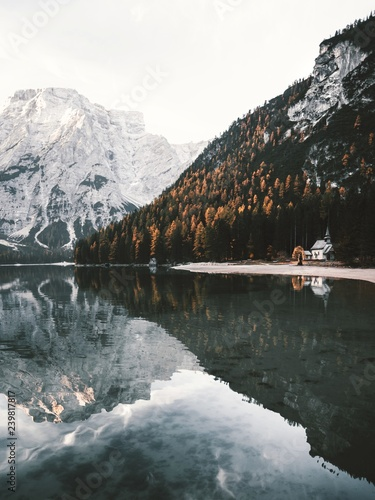Leinwanddruck Bild Calm morning at the Braies lake in autumn.Beautiful mountain reflections on water.