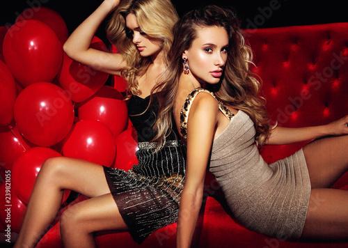Leinwanddruck Bild Two sexy girls on lounge. Celebrating.