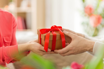 valentines day, greeting and people concept - close up of male and female hands with gift box