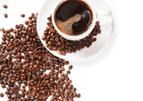 Cup of strong coffee in roasted coffee beans on white background, isolated