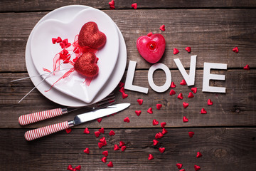 White plates in form of heart, cutlery, decorative hearts, candle  and word love on  vintage textured  background. © daffodilred