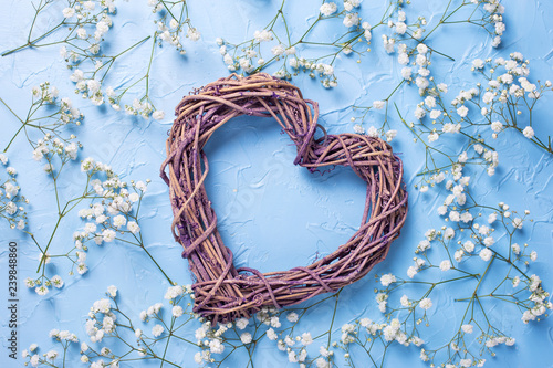 Big decorative heart and p attern from fresh white gypsofila  flowers on blue textured background. - 239848860
