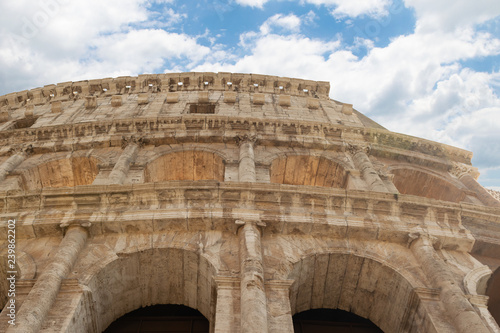 Beautiful detail of Roma Colosseum against blue sky with clouds