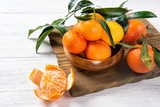 Mandarine or tangerine with leafs on wooden table, winter fruits