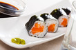 Maki rolls with salmon served with wasabi and soy sauce on white plate