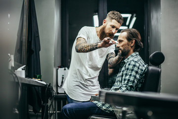Confident man smiling while his barber working © shevchukandrey