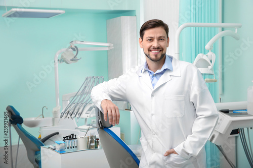 Leinwanddruck Bild Professional male dentist in white coat at workplace. Space for text