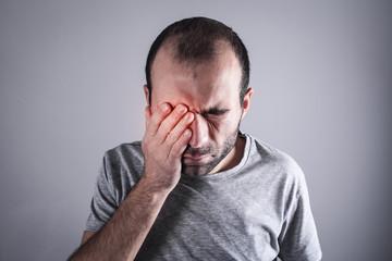 Caucasian man with eye pain. Eye disease