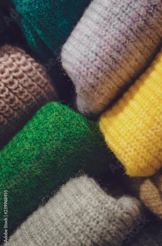 folded clothes in the store, colored sweatshirts and sweaters folded up on the shelves of the store, backgrounds for the text or advertisements of women's clothing store or showroom - 239968455