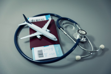 travel insurance - passport with flight ticket and stethoscope on gray background