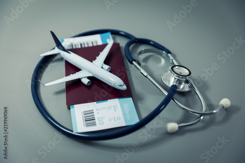 Foto Murales travel insurance - passport with flight ticket and stethoscope on gray background