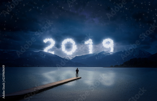 Acrylglas Pier New year background, young man standing on a jetty in a lake and looking to the mountains under the dark sky with cloudy text 2019