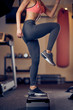 Leinwanddruck Bild - Smiling Caucasian blonde woman with ponytail in sportswear doing exercises on steps . Gym interior, healthy lifestyle concept.