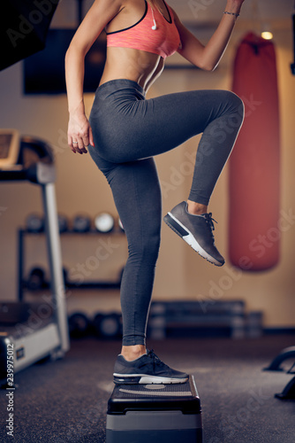 Leinwanddruck Bild Smiling Caucasian blonde woman with ponytail in sportswear doing exercises on steps . Gym interior, healthy lifestyle concept.