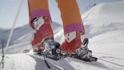 4K winter sport footage, close up female skier woman stepping in ski binding strap on skies on piste skiing away on sunny winter day in mountains with snow