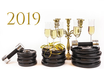 Glasses of champagne on weight plates and dumbbells. Concept for new years resolution 2019 and workout, exercise more next year.  - image © Forenius