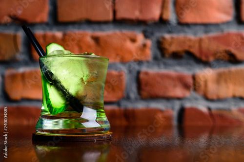 Gin Tonic Cocktail with cucumber and ice in a glass on the wooden tray on the dark background