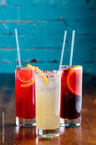 row of various colourfull alcoholic cocktails on a bar desk