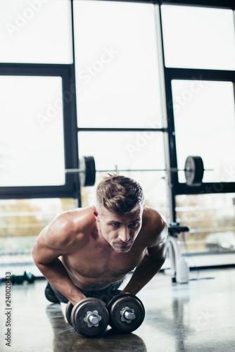 handsome shirtless sportsman doing plank on dumbbells in gym