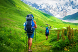 Couple of young travelers hiking with backpacks on beautiful grassy trail in Alps mountains.