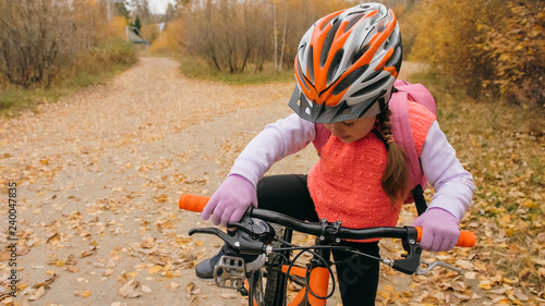 One caucasian children walk with bike in autumn park. Little girl walking black orange cycle in forest. Kid goes do bicycle sports. Biker motion ride with backpack and helmet. Mountain bike hardtail.
