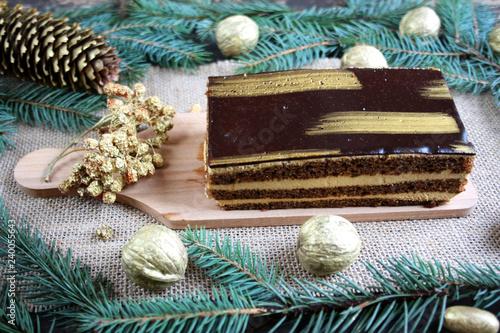 Orzechowe złote ciasto pośród bożonarodzeniowych dekoracji, złotych orzechów, jarzębiny i szyszek