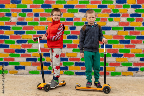 Village children ride scooters and take pictures on the background of a multi-colored brick wall