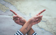 Crossed hands with forefingers show opposing directions