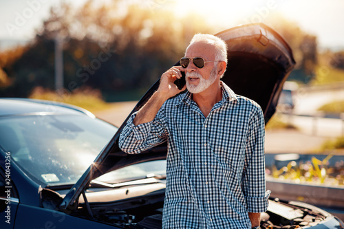 Senior man having problem with a car