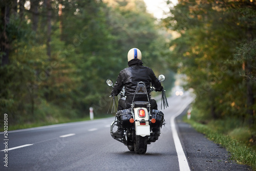 Back view of biker in black leather jacket and white helmet riding motorbike along hilly road between tall green trees. Active lifestyle, love to adventures concept.