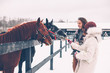 Teen girl and her father feeding horses on the ranch
