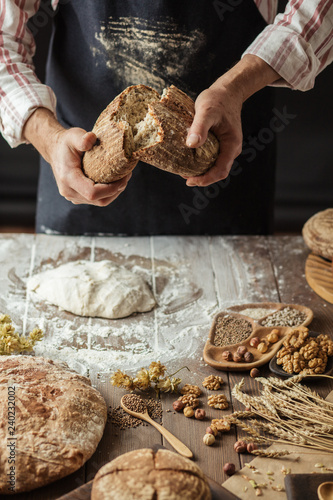 Leinwanddruck Bild Man breaking off piece of rustic rye bread, standing at table with dough in flour, closeup