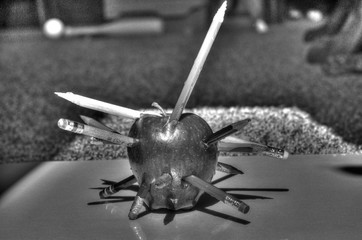 Punctured apple with pencils