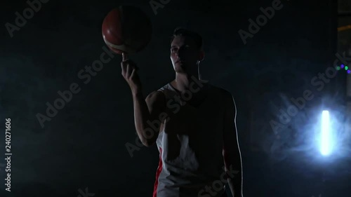 A man in sports form rotates a basketball on his finger performing a trick looking at the camera on the basketball court around the smoke in slow motion.