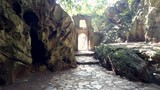 motion along high stone walls in yard to ancient arch at famous marble cave on sunny tropical day - 240280039