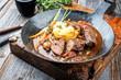Leinwanddruck Bild - Traditionelle deutsche geschmorte Schweinebäckchen in brauner Rotwein Sauce mit Pilzen und Kartoffel Püree als closeup in einer schmiedeeisernen Pfanne