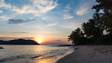 Beautiful charming sunset by the sae on the beach of Phu Quoc island with beautiful view of palms,mountains and orange sky
