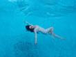 Leinwandbild Motiv schöne erwachsene Frau im besten Alter mit dunklen Locken im weißen Kleid schwebt schwerelos elegant glücklich schwimmend in türkis blauem Wasser im Pool