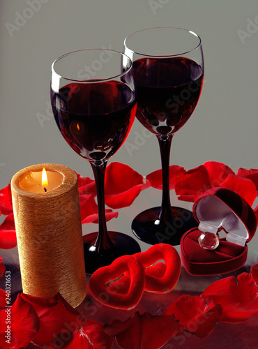Two glasses of red wine and burning candle
