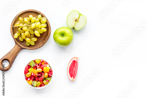 Healthy diet concept. Fruit salad near fresh fruits on white background top view space for text - 240325456
